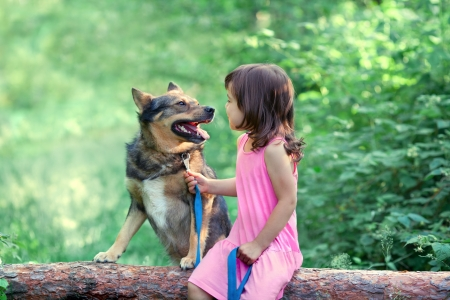 snag: Happy little girl with dog sitting on the snag in the wood Stock Photo