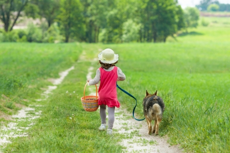 Little girl with dog running on the road to the picnic photo