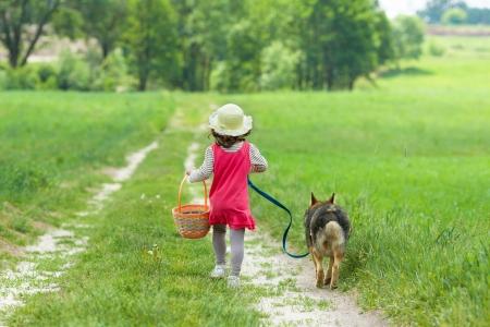 Petite fille avec le chien qui court sur la route pour le pique-nique