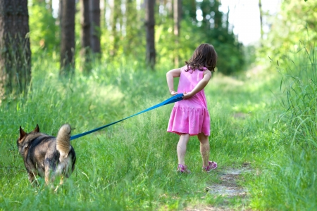 Little girl with dog running on the road in the forest photo