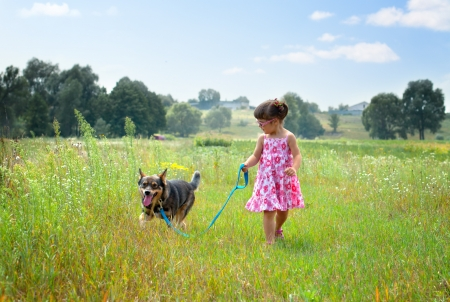 Little girl walking with dog at the meadow and keeping the dog on leash photo
