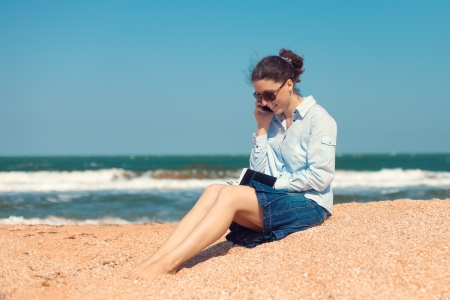 Business woman talking on mobile phone on the beach photo