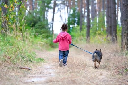 Little girl with dog walking on the road  Back to camera
