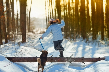 Young woman with her dog jumping over a log in snowy winter Stock Photo