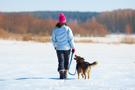 Young woman with her dog walking on the snowy field photo