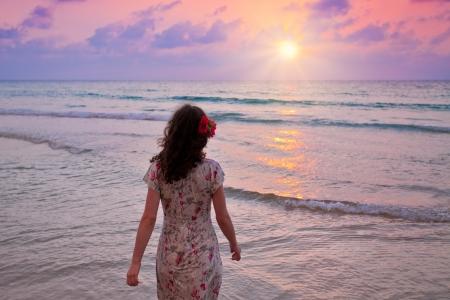 seashores: Young woman walking on seashore at sunset and looking at the sun
