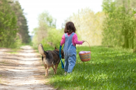 Little girl with dog walking on the road photo