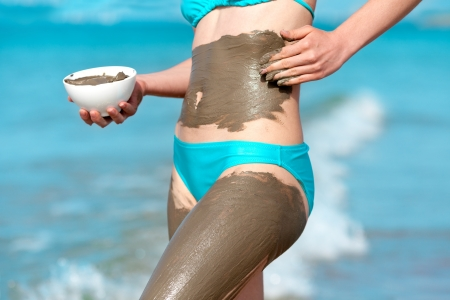 Woman smearing mud mask on the body photo