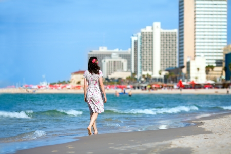 Young woman walking on the beach in Tel-Aviv photo