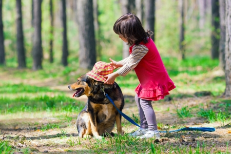 Little girl putting hat on the dog in the wood photo