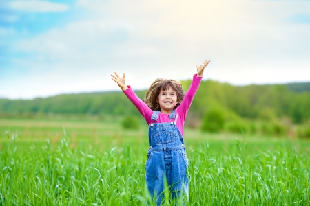 Happy little girl with her hands up on the green wheat field Stock Photo