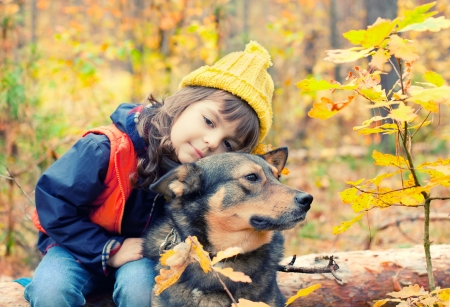 Little girl with big dog in the forest in autumn