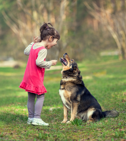 Happy little girl talking to dog photo