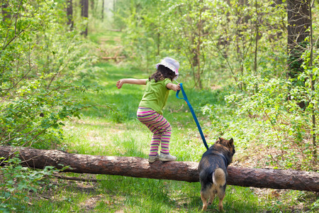 Little girl with her dog jumping over a log in the forest photo