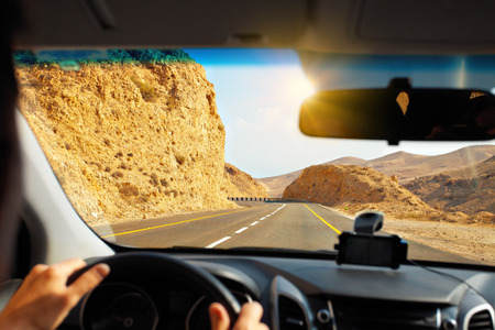 Driving a car on mountain road to Dead Sea photo