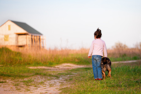 country house: Little girl with dog walking in the countryside at sunset back to camera