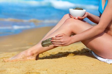 sal: Mujer manchas máscara de barro en el cuerpo en la playa Foto de archivo
