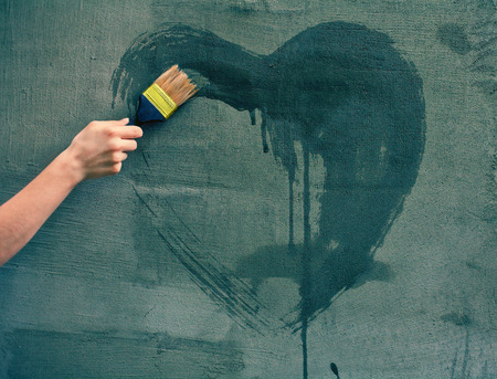 Female hand painting heart on the concrete wall photo