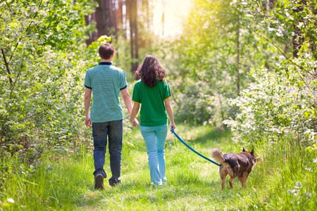 2 way: Young couple holding hands and walking with their dog in the forest