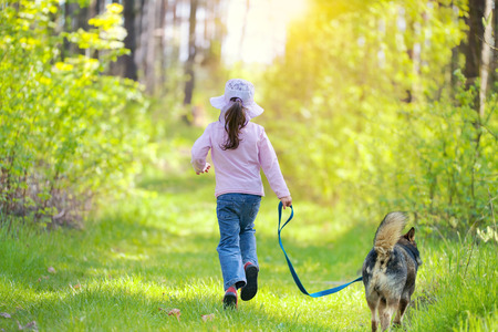 Little girl with dog running in the forest  Back to camera  photo