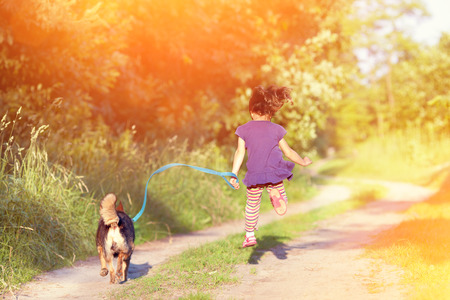 sun light: Little girl with dog running in the countryside