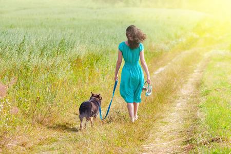 persona cammina: Giovane donna che cammina con il cane