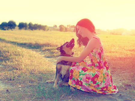 Young happy woman with dog on the meadow at sunset