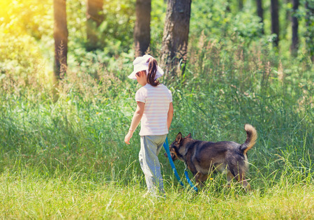 Little girl with dog walking in the forest photo