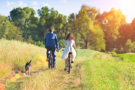 Young happy bride and groom ride bicycles in the meadow back to camera and holding hands photo