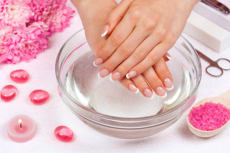 Beautiful woman s hands with perfect french manicure decorated with chrysanthemum flower Stock Photo