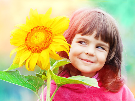 Little girl with sunflower photo
