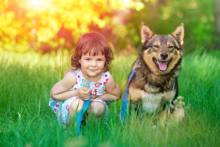 Happy little girl sitting with dog on the grass photo