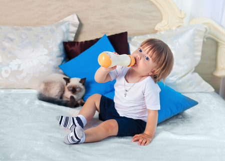 Little boy drinking milk from bottle on the bed photo