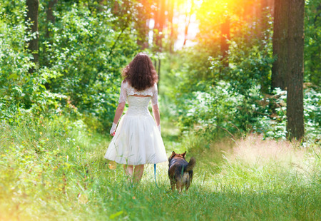 Young bride walking with dog in the forest photo