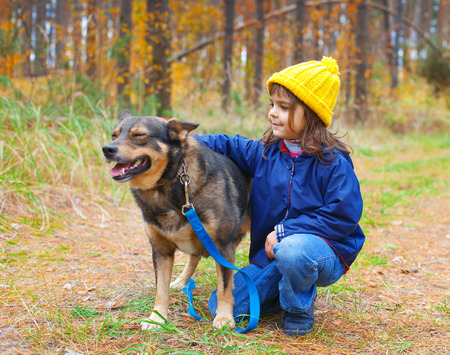 Happy little girl playing with big dog in the forest in autumn Stock Photo