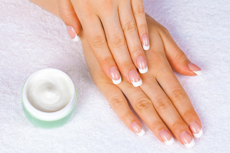 Spa hands with perfect french manicure near jar of cream photo