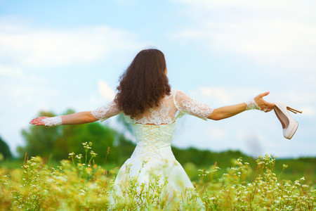 Young bride walking on the flower meadow holding shoes photo
