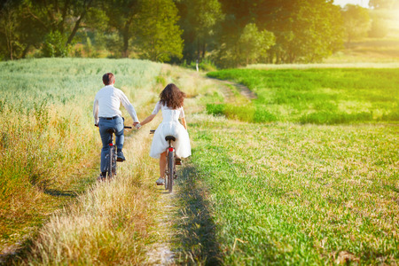 Young happy bride and groom ride bicycles in the meadow back to camera and holding hands. Stockfoto