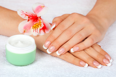 Female hands with french manicure near jar of cream on white towel