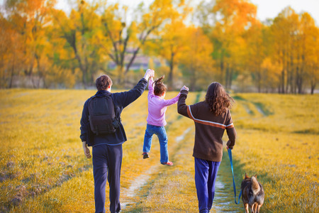 fall time: Family with dog walking in the forest back to camera Stock Photo