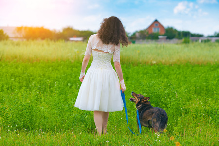 Young bride walking with dog in the field photo