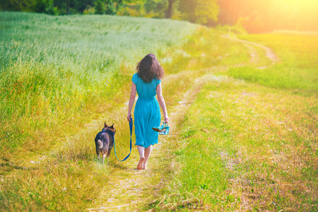 Young woman with her dog walking in the field photo