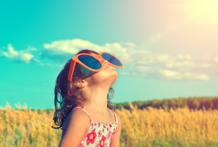 sol: Niña feliz con grandes gafas de sol mirando al sol Foto de archivo