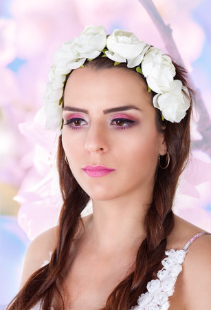 Portrait of beautiful girl with bright makeup. Woman with brown eyes and chaplet photo