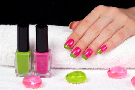 Beautiful female hand with two-color manicure on white towel on black background photo