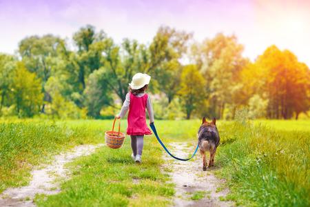 Petite fille avec un chien courir sur la route pour le pique-nique