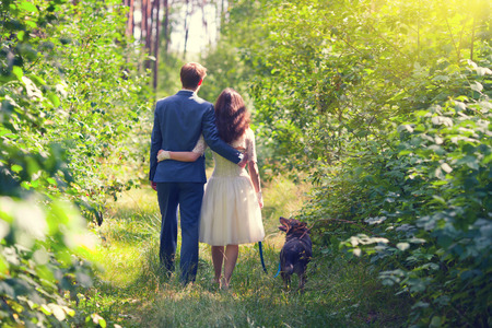 Young hugging newlyweds walking with dog in the forest back to camera photo