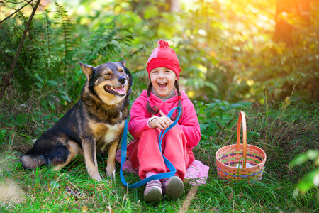 jungle girl: Happy little girl with dog relaxing in the forest