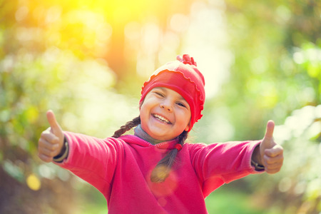 up country: Happy little girl showing thumbs up in sunny day