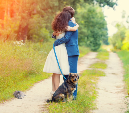 dog leashes: Young couple hugging in the forest. Dog and cat sitting near the couple. Stock Photo